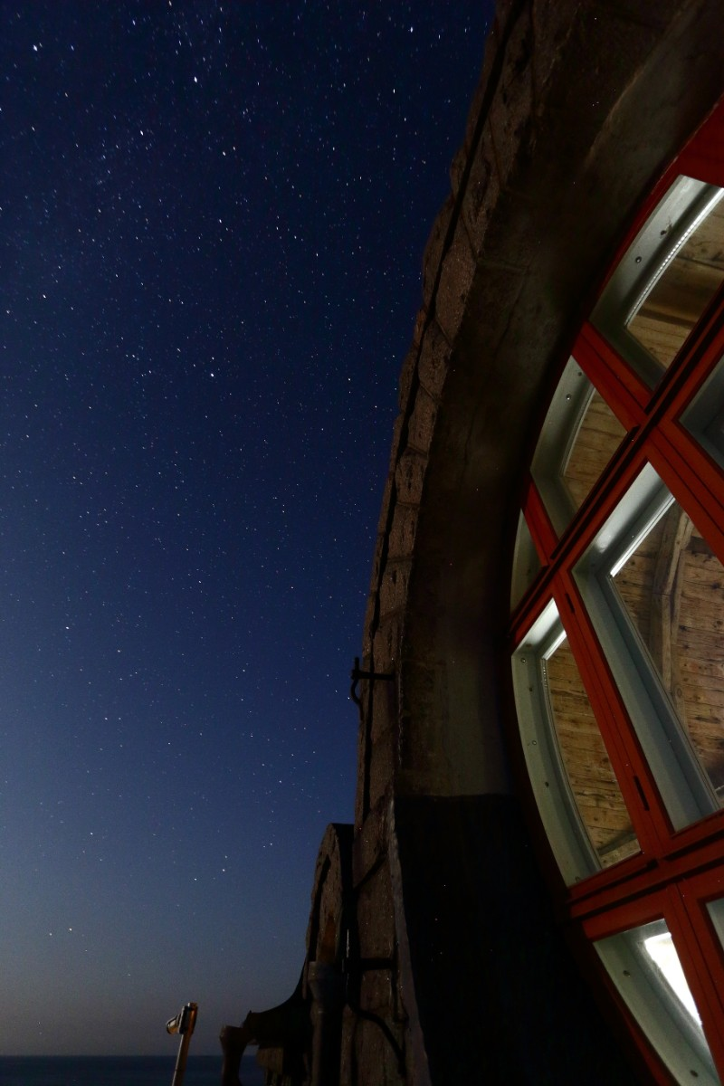 Photo of the lighthouse's large window at night.